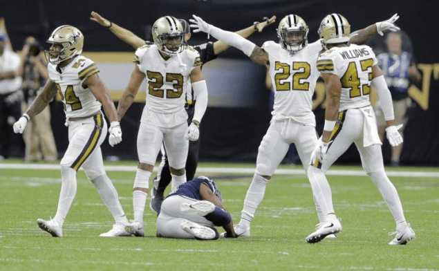 saints defense in white color rush jerseys celebrate after play with cowboys receiver on turf