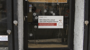 bullet holes in glass door of cell phone store in philly