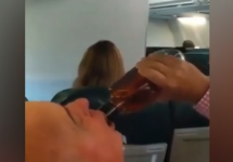 man chugging whiskey from the bottle in an airplane