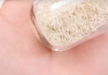 glass jar of fingernail clippings in the palm of hand