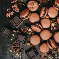 chocolate and chocolate macaroons scattered on table