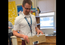 teacher holding gifted box of shoes