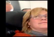 woman looking backwards in airplane