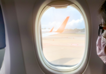 woman wearing a mask looking out airplane window